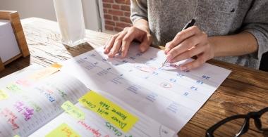 Businesswoman Marking Schedule On Calendar